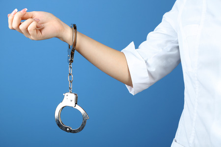 handcuffed: Female hand is handcuffed at  wrist on blue background Stock Photo