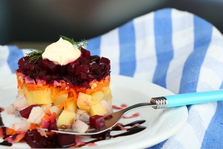 ensaladilla rusa: Russian herring salad on plate on wooden table, on dark background
