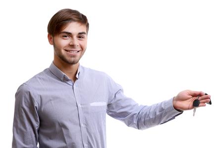 Businessman holding car key isolated on white Banco de Imagens