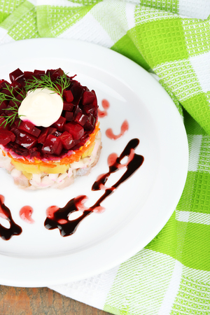 ensaladilla rusa: Russian herring salad on plate on wooden table background