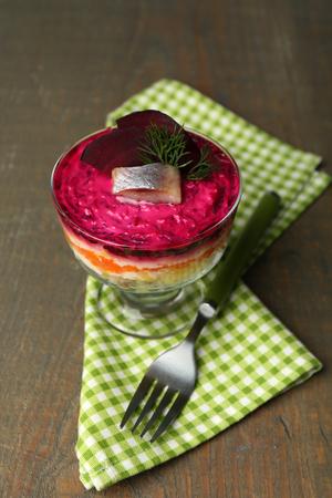 ensaladilla rusa: Russian herring salad in glass bowl on wooden table background Foto de archivo