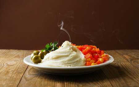 Delicious home cooked food with steam on table on brown background Stock Photo