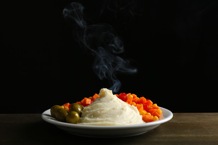 Delicious home cooked food with steam on table on black background