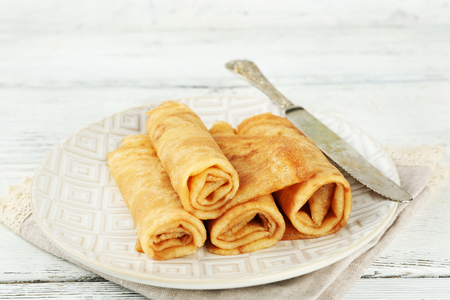 Plate of delicious pancakes on wooden background