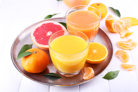 Grapefruit and tangerine juices on wooden table