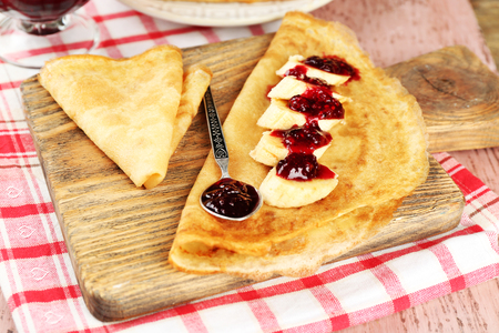 Delicious pancakes with berry jam  and bananas on wooden board, on wooden background