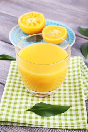 Glass of juice and ripe sweet tangerine on wooden table