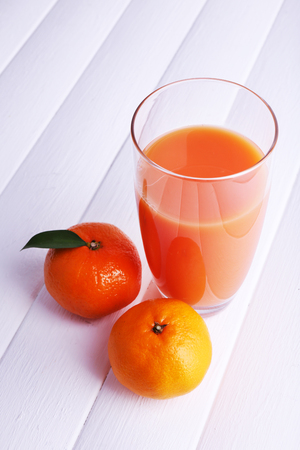 Glass of juice and ripe sweet tangerine on white wooden table