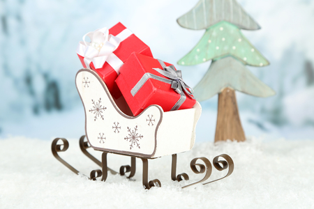 Wooden toy sledge with Christmas gifts  on nature background Stock Photo