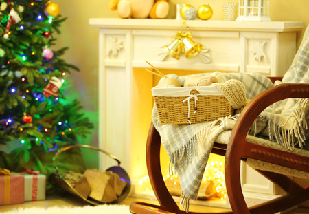 Beautiful Christmas interior with decorative fireplace and rocking armchair
