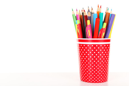 Colorful pens, pencils and markers in red polka-dot plastic cup isolated on white background 版權商用圖片