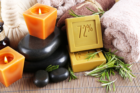 Handmade soap with the branches of rosemary,  spa stones and towels, close-up. Rosemary spa concept
