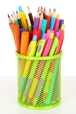 Colorful pens and pencils in green metal vase isolated on white background