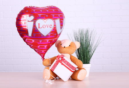 Teddy bear takes gift and love heart balloon with plant on wooden table, on the brick wall background
