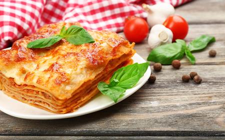 Portion of tasty lasagna on wooden table Foto de archivo