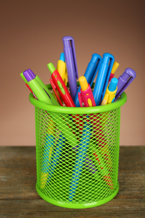 Colorful pens in green metal holder on wooden table and shaded color background