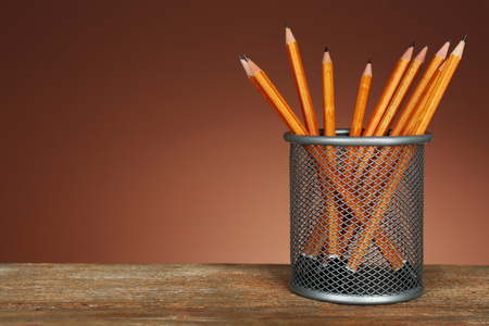 Many pencils in metal holder on wooden table and shaded color background