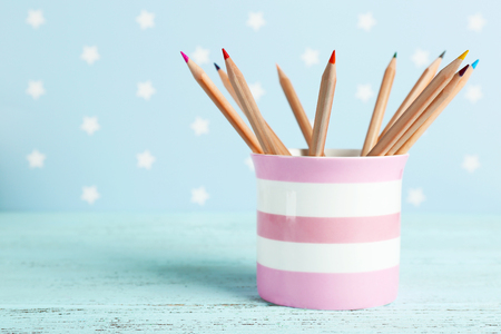 Plastic cup with different pencils on color wooden table on color wooden table and blue background with printed stars