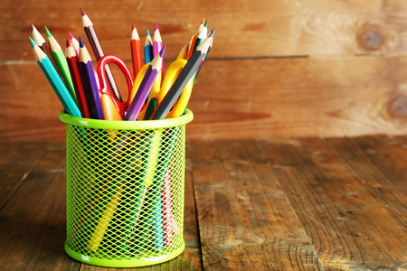 Colorful pencils with scissors in metal holder on rustic wooden background Foto de archivo