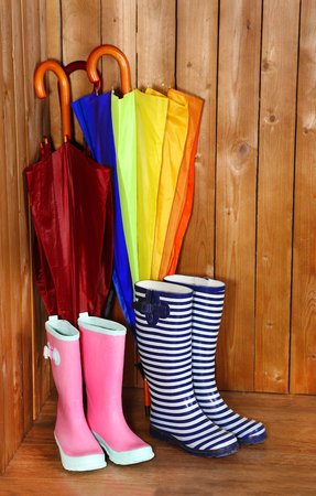 Bright umbrellas leaning against a wooden wall and gumboots