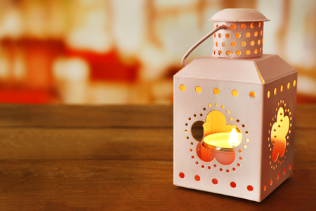 Lantern on wooden surface and blurred background