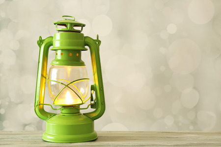 Oil lamp on wooden surface and blurred background