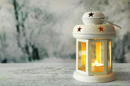 Lantern on wooden surface and winter background Stock Photo