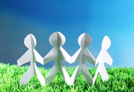 Paper group of people holding hands on green grass on blue background Stock Photo