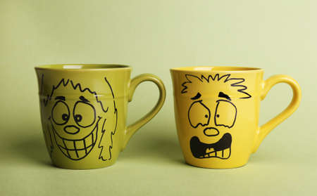 Emotional cups on green background Stock Photo