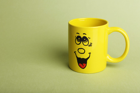 Emotional cup on green background Stock Photo