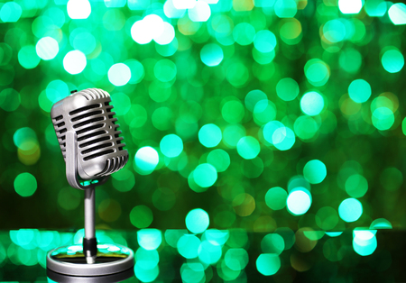 Silver microphone on green background