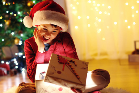 Little boy sitting near fireplace in room Stock Photo
