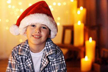 Little boy sitting near fireplace in room Stockfoto