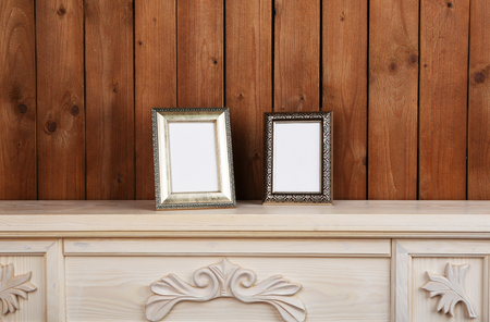 Photo frames on chest of drawers, on wooden wall background Stock Photo