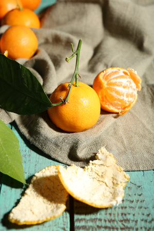 Juicy ripe tangerines with leaves on wooden table  Stock Photo