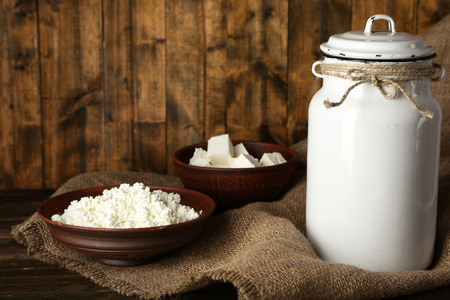 Milk can with cottage cheese on rustic wooden background Stock Photo