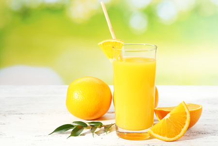 Glass of orange juice with straw and slices on wooden table and bright background