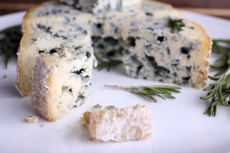 Blue cheese with sprigs of rosemary on plate, closeup view