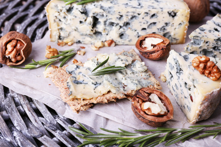 Blue cheese with sprigs of rosemary and nuts on wicker mat background
