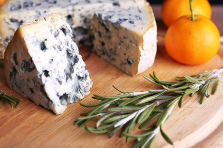 Blue cheese with sprigs of rosemary and oranges on board and wooden table background 免版税图像