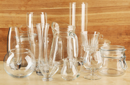Different glassware on wooden background Imagens