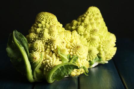 Romanesco broccoli on wooden table, on dark background