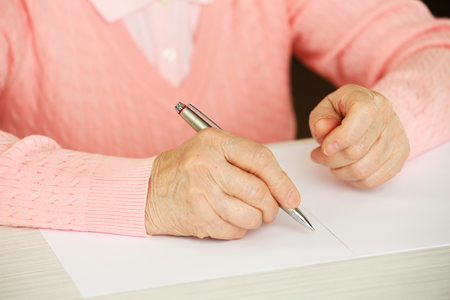Hands of adult woman writing, on table, on light background Imagens