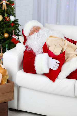 Santa Claus sleeping at home near Christmas tree