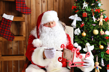 Santa Claus sitting in comfortable rocking chair and decorated presents near Christmas at home