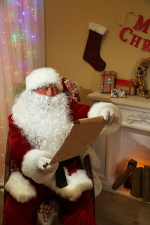 Santa Claus sitting with list of presents in comfortable chair near fireplace at home Stock Photo