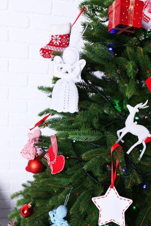Knitted Christmas angels on Christmas tree, close-up