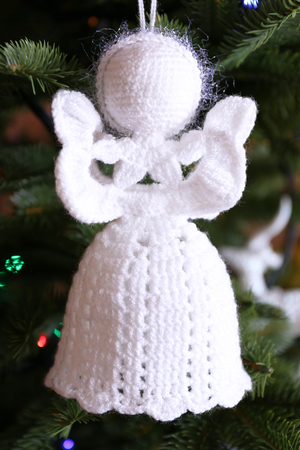 knitted christmas angels and other decorations on christmas tree background close up stock photo