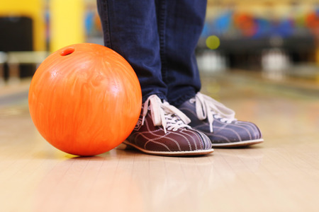 Male legs and bowling ball in alley background Stock Photo