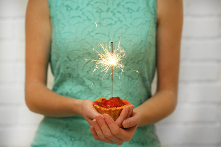 Woman holding tasty cake with sparkler, on grey wall background